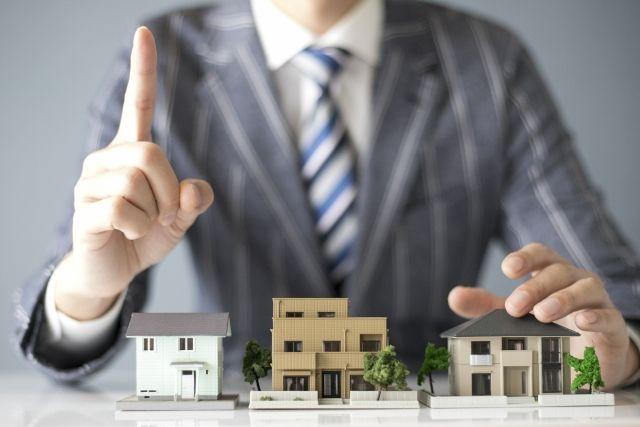 家の模型を並べて紹介するビジネスマン
