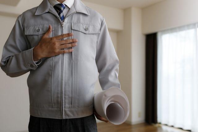 見取り図を持った作業服姿の男性